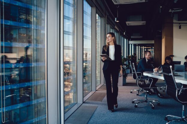 female executive with tablet walking through office